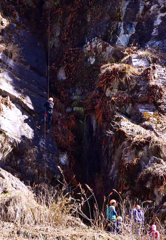 Adventure activities in Chopta - a girl trying to rappel down from a rock in Chopta - activities done by Magpie camp