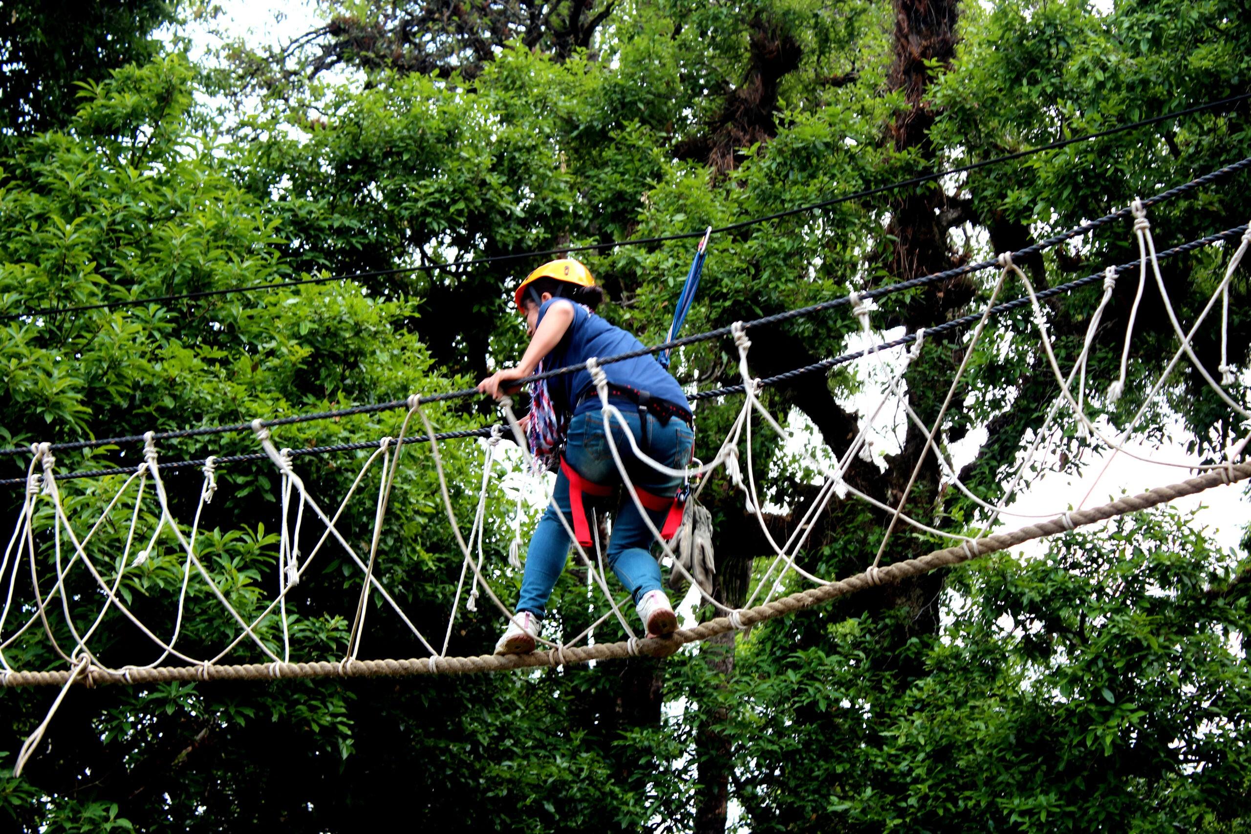Obstacle activities in Magpie chopta - A girl crossing a burma bridge in Chopta